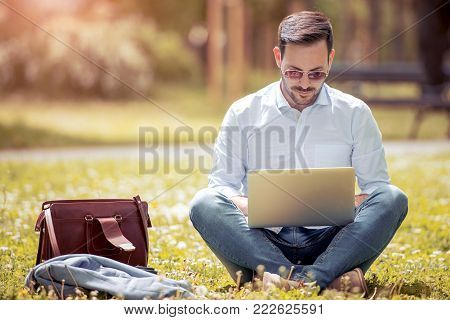 Young Attractive Man Sitting  On Concrete While Using Phone.