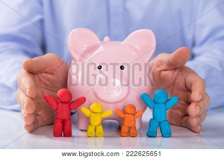 Hand Protecting The Pink Piggybank With Colorful Family Made Up Of Clay On Desk