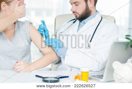 Vaccination.  Flu shot. Doctor with syringe making vaccination to patient.  Doctor making an injection to girl