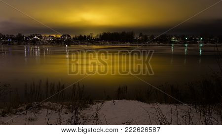 View of Neva River at evening when the clouds reflected the light from the city lights on the outskirts of St. Petersburg, Russia. Long exposure.