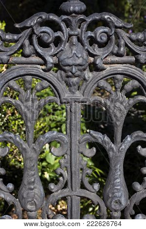 A ornate fence in downtown Columbia, South Carolina looks lace made of wrought iron with a face of a bearded man as the focal point