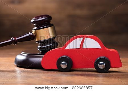 Wooden Toy Red Car In Front Of Judge Gavel On The Wooden Table Background