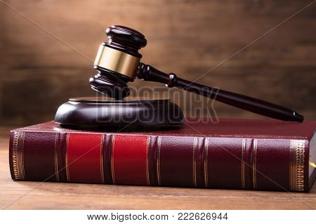 Close-up Of Judge Gavel And Soundboard On Law Book Over The Wooden Desk