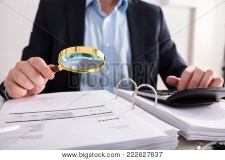 Close-up Of A Businessperson's Hand Checking Invoice Through Magnifying Glass At Workplace