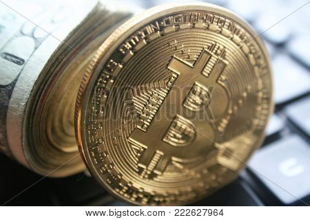 Gold Bitcoin Close Up With A Roll Of Twenties On Computer Keyboard Stock Photo