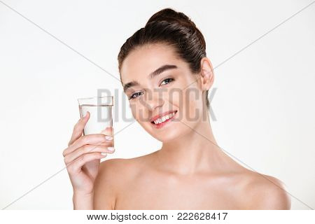 Close up picture of glad gorgeous woman being half-naked drinking minaral water from transparent glass with smile, over white background