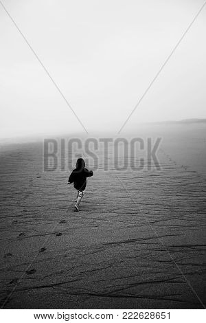 Black and white kid running on a foggy beach into the unknown