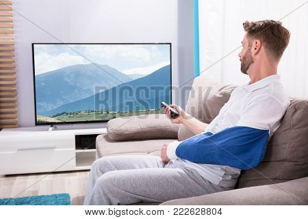 Young Man With Fractured Hand Sitting On Sofa Watching Television At Home