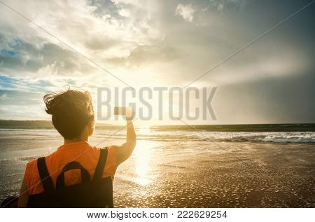 woman with a backpack and a smartphone takes pictures of a beautiful sunset, ocean and stormy sky on a tropical beach.