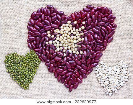 Valentines Day Heart Made of Red Bean, Green Bean, and Pivot on Brown Sackcloth Background. with copy space for your text.
