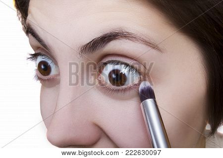 Young woman doing makeup on white background