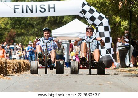 ATLANTA, GA - SEPTEMBER 2017: Two men race each other on adult big wheels in a friendly competition at the East Atlanta Strut, a fall festival in Atlanta, GA on September 23, 2017.