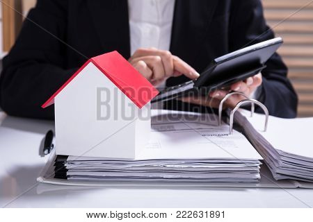 Businesswoman Calculating Financial Data With House Model On Desk