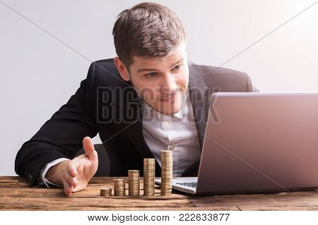 Businessman Working On Laptop With Stacked Coins On Wooden Desk