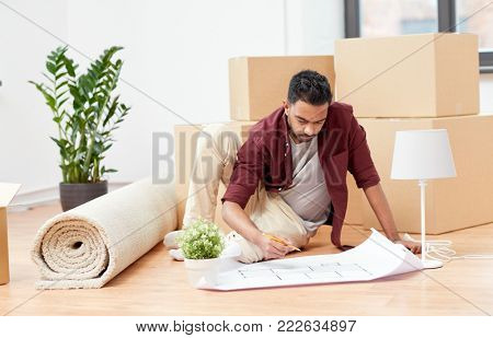 moving, people and real estate concept - indian man with blueprint and boxes at new home