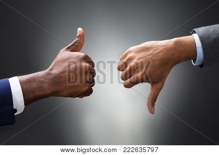 Two Business People Showing Thumbs Up And Down Sign Against Gray Background