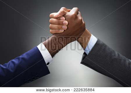 Close-up Of Two Businessman Competing In Arm Wrestling On Gray Background