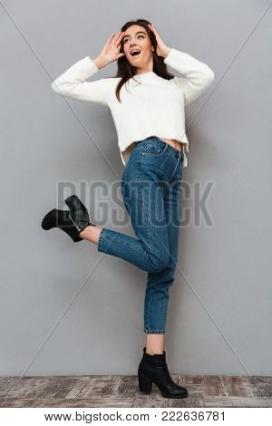 Full-length portrait of amazed stylish woman in white fluffy pullover and jeans standing on one leg, looking aside, isolated on gray background