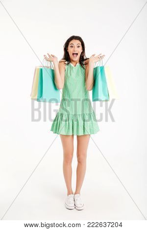Full length portrait of a happy girl in dress holding shopping bags and screaming isolated over white background