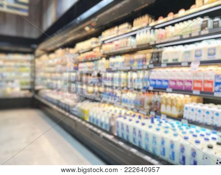 Grocery store blur background or blurry supermarket with shelves of food products and diary supplies in refrigerator shelves display
