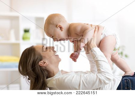 Mother and baby boy in diaper playing in sunny room. Parent and little child relaxing at home. Family having fun together.