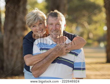 portrait of American senior beautiful and happy mature couple around 70 years old showing love and affection smiling together in the park having a romantic walk relaxed enjoying retirement