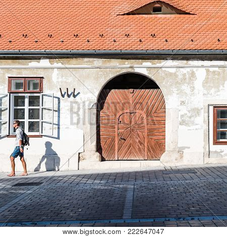 Budapest, Hungary - August 12, 2017:  Unidentified man walking at exterior door of residential building in the old city of Buda in Budapest.