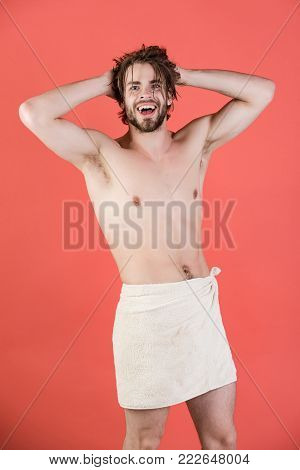 Refreshment, healthcare. Hygiene, sexy guy wash, spa, relax. Man with wet hair hold towel after shower. Man in bathroom with muscular body on red background. Morning washing, wake up, everyday life.