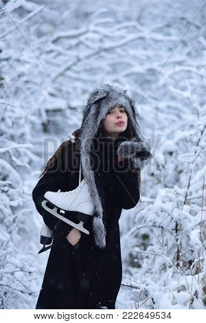 Vacation, holidays, hobby, lifestyle. Woman with skating shoes in winter clothes in snowy forest. Ice skating concept. Sport, activity, health. Girl with pair of figure skates at trees in snow.