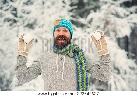 Bearded man smile with snowballs in snowy forest. Hipster in thermal jacket, hat, scarf, beard warm in winter. Skincare, beard care in winter. Temperature, freezing, cold snap. Snow fight, sport, rest