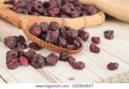Dried cranberries are in the wooden spoon