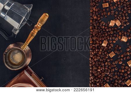 top view of roasted coffee beans with sugar, coffee pot, coffee maker and grinder on black