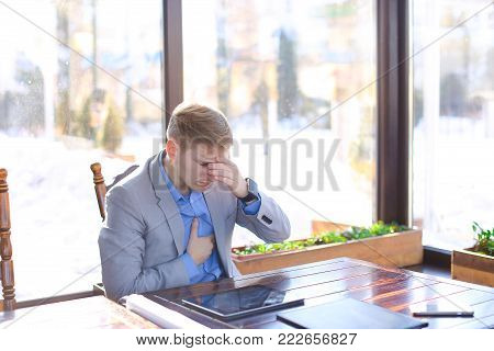Tired man of architectural faculty using tablet at cafe with roll project and black document case on table. Young exhausted guy sitting at catering establishment and working. Concept of gadgets and resting after work.