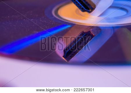 Closeup Of White Hdmi Cable With It's Reflection On Blank Disc