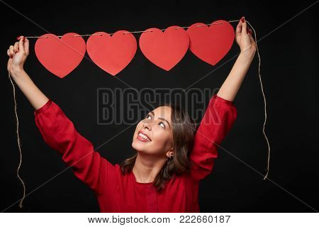 Woman in red lifting above her head a thread with four red heart shapes beaded on it, looking up, over dark background