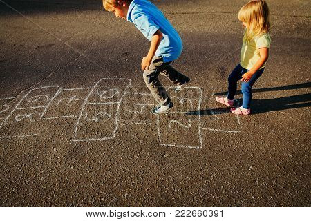 little boy and girl playing hopscotch on playground outside
