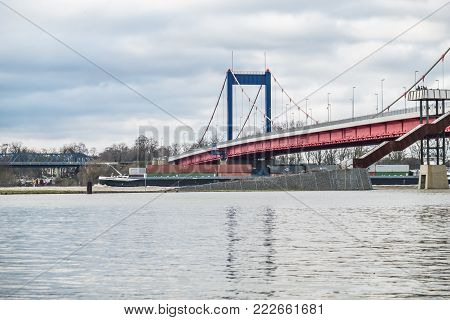 DUISBURG , GERMANY - JANUARY 08 2017 : Container ship is passing the bridge over the river Rhine in Ruhrort during the flooding