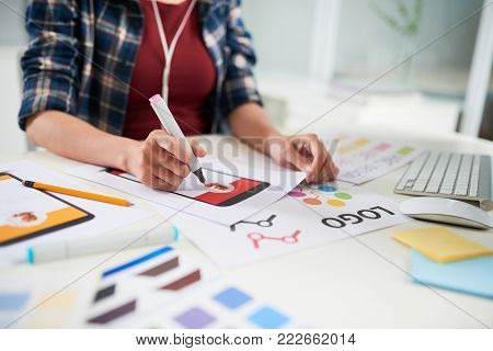 Close-up shot of unrecognizable student sitting at desk and wrapped up in making wall newspaper, blurred background