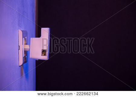 WiFi repeater in electrical socket on the wall. Device that help to extend wireless network in home or office.
