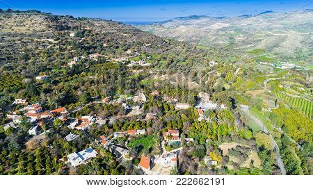 Aerial bird eye view of Miliou village hills and Akamas sea at Latchi, Paphos Cyprus. View of traditional ceramic tile roof houses near Ayii Anargyri monastery nature hotel spa from above.
