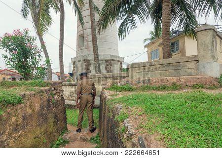 Galle, Sri Lanka - Dec 23, 2017: Policemen In Retro Uniform Walk Past Historical Lighthouse On Decem