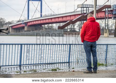 DUISBURG , GERMANY - JANUARY 08 2017 : Tourist observing the the river Rhine flooding the promenade and streets in Ruhrort