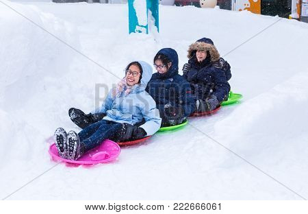 Hokkaido, Japan - 28 December 2017 - Group of happy Asian tourists enjoy their snow slider ride at a public park in Hokkaido, Japan on December 28, 2017
