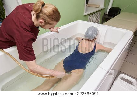 Young woman during hydromassage in beauty spa salon. Underwater hydrotherapy massage procedure