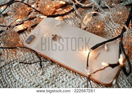 KIEV, UKRAINE - OCTOBER 25, 2017: Modern gold iPhone 8 plus with decor on fabric