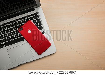 KIEV, UKRAINE - OCTOBER 17, 2017: Red iPhone 7 plus on MacBook