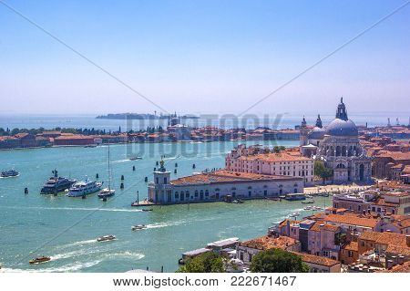 Panorama  of Italian houses with red tiled roofs, Adriatic sea and Grand Canal with boats and gondolas, ships and boats, romantic city on water, Venice, Italy. Top view.