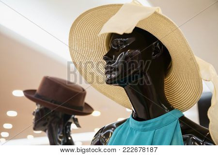 Sad lady manikin wearing a straw hat in a shop window. Pensive mannequin woman presents summer fashion style in a clothing store