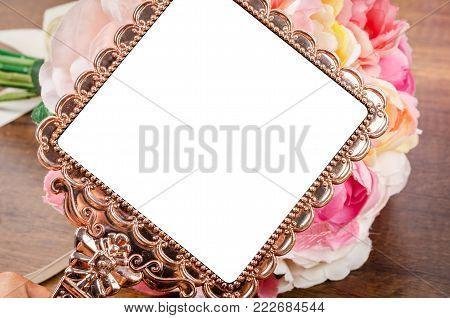 Beautiful pink gold mirror with rose on wooden background. Save clipping path.
