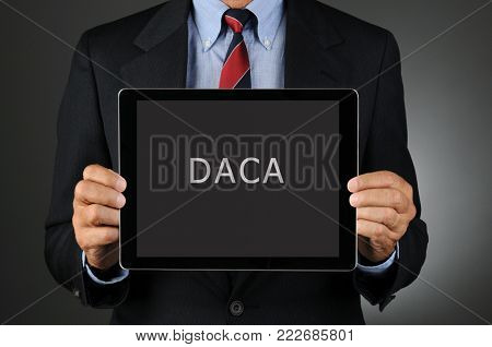 Closeup of a Congressman holding a tablet computer in front of his torso with the Acronym DACA. Man is unrecognizable.